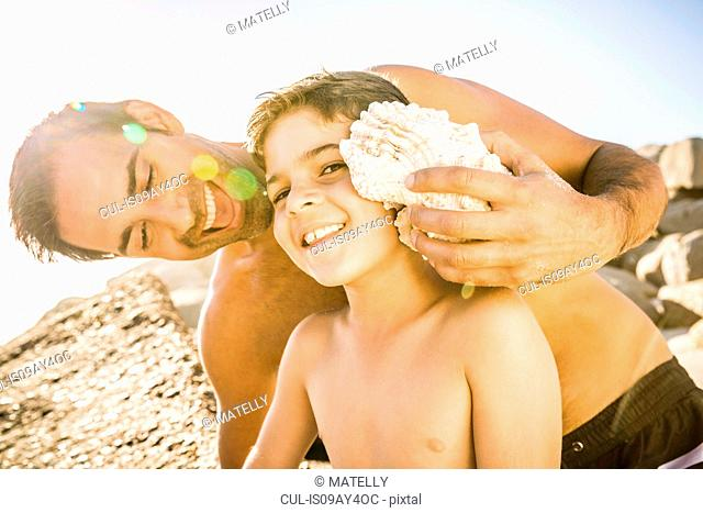 Father holding seashell to son's ear to hear the ocean
