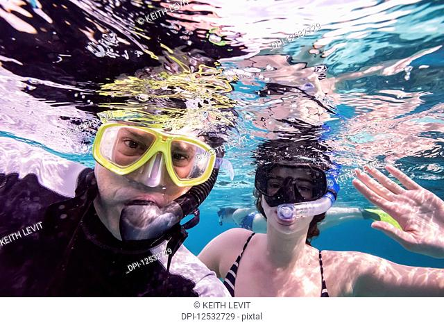 A man and his daughter snorekling and posing for the camera underwater, Turneffe Atoll; Belize