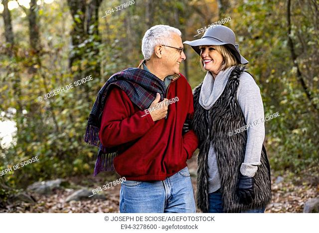 A happy 65 year old man and a 59 year old blond woman hugging and smiling at each other in a forest setting