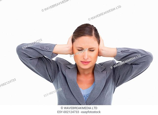 Close up of annoyed tradeswoman covering her ears against a white background