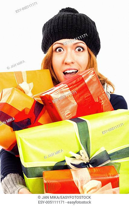 Ecstatic happy woman in winter hat holding many colorful gift boxes, isolated on white background
