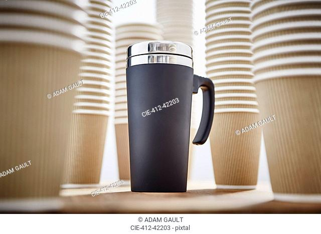 Insulated drink container surrounded by disposable coffee cups