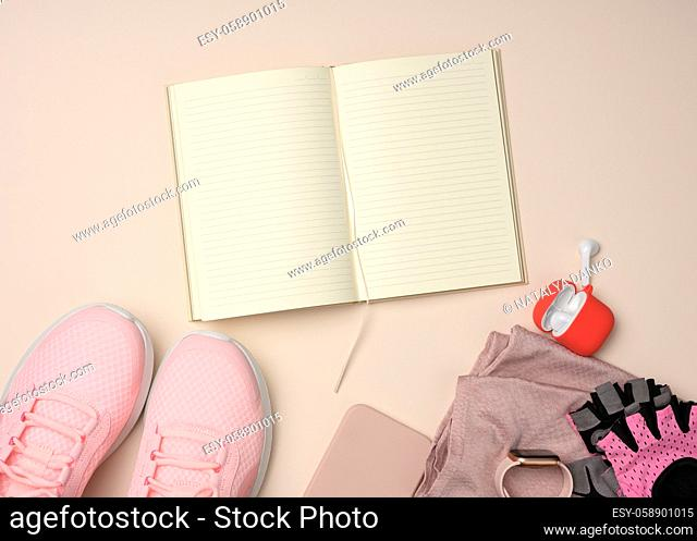 open notebook with blank pages, pink sneakers and smart gadgets on a beige background. Place to record goals and achievements, schedule, flat lay