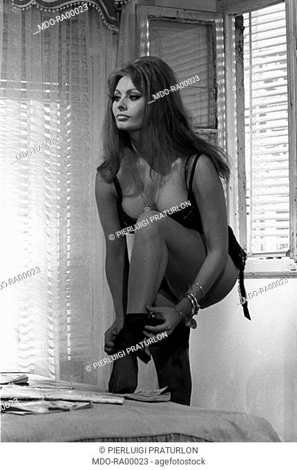 The Italian actress Loren Sophia, as a prostitute, undressing, taking off her nylon stockings, on the set of the film Yesterday, today and tomorrow