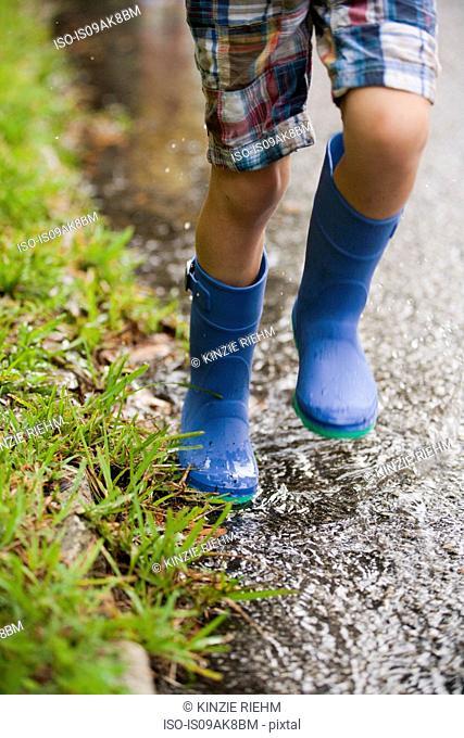 Legs of boy running wearing rubber boots