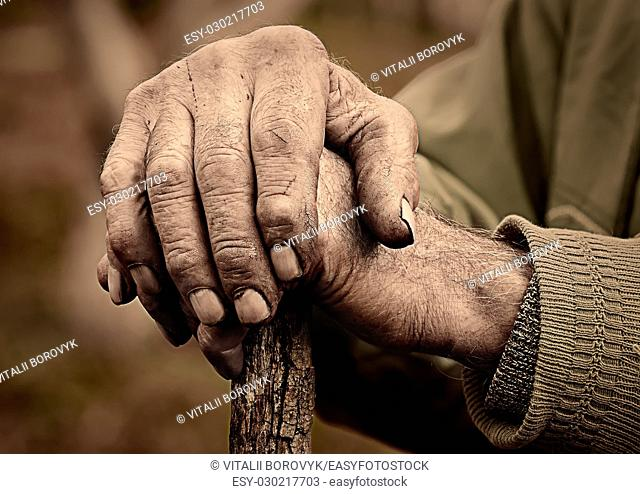 Dramatic photo of an elderly man hand holding a staff