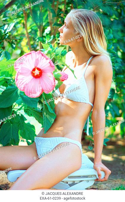 Woman in bikini sitting next to large flower outdoors