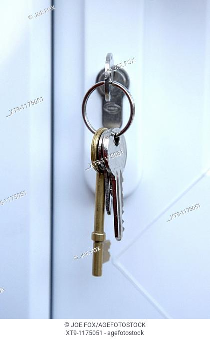 set of house keys left hanging from the lock of a pvc double glazed door