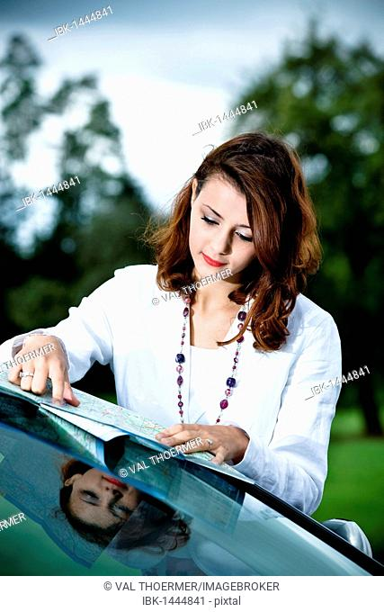 Young woman looking at a road map on a car