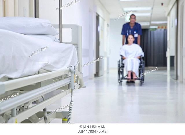 Male Nurse Pushing Patient Along Hospital Corridor In Wheelchair