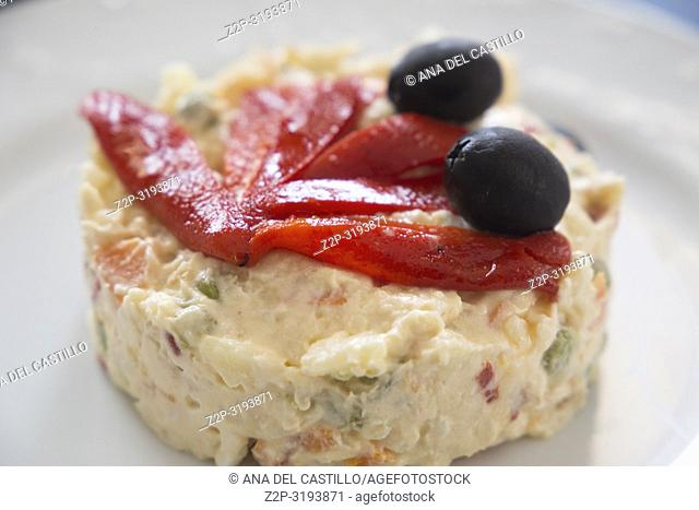 Russian salad with red peppers and black olives on plate
