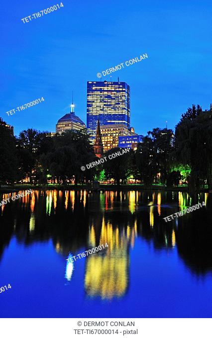 Office building reflecting in pond in Public Gardens at dusk