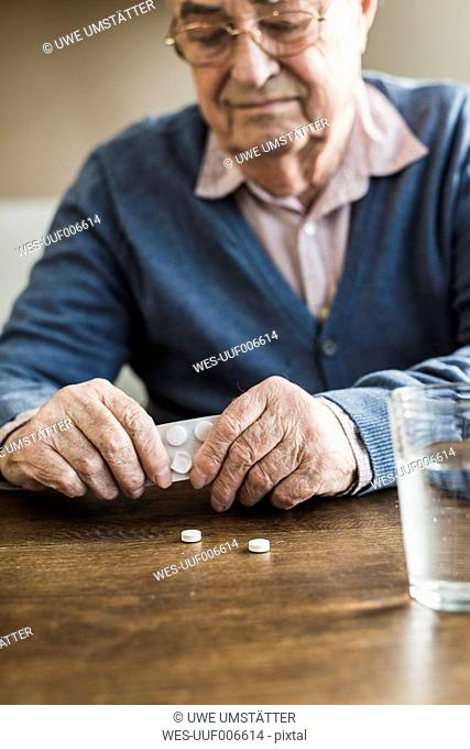 Senior man taking tablets out of blister pack, close-up