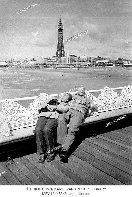 An elderly couple lie back on the wrought iron seats on Blackpool Pier for a snooze. The beach and Blackpool Tower are in the background