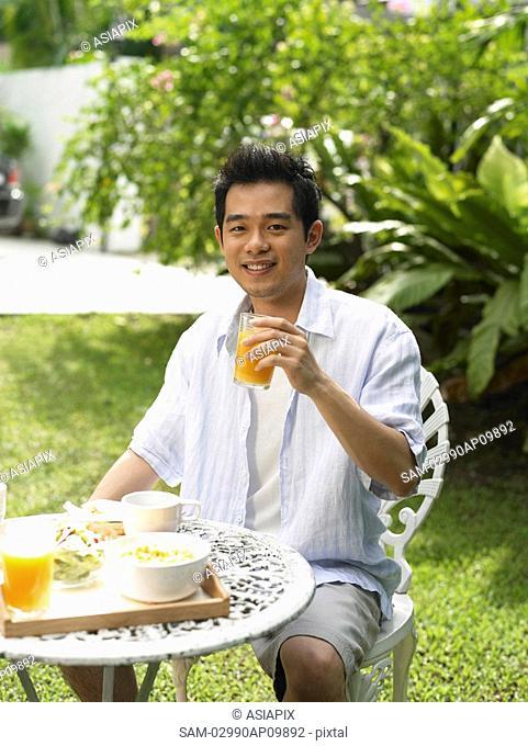 man having breakfast outside