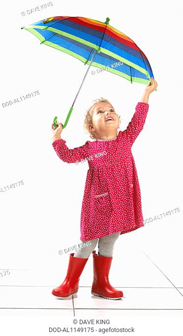 Small girl (2 years) wearing wellington boots and holding umbrella