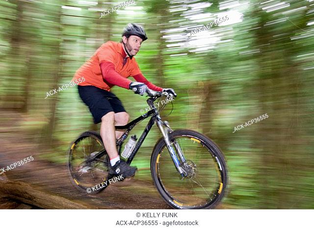 A male mountain biker makes his way down a trail near Powell river on the upper Sunshine coast area of the Vancouver coast and mountain range, British Columbia