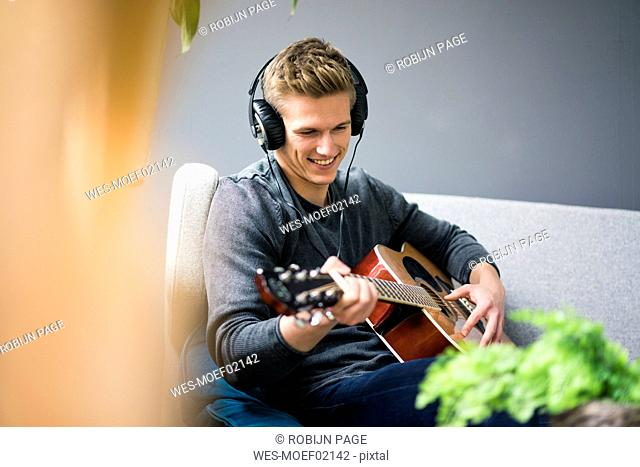 Smiling young man with headphones sitting on couch playing guitar