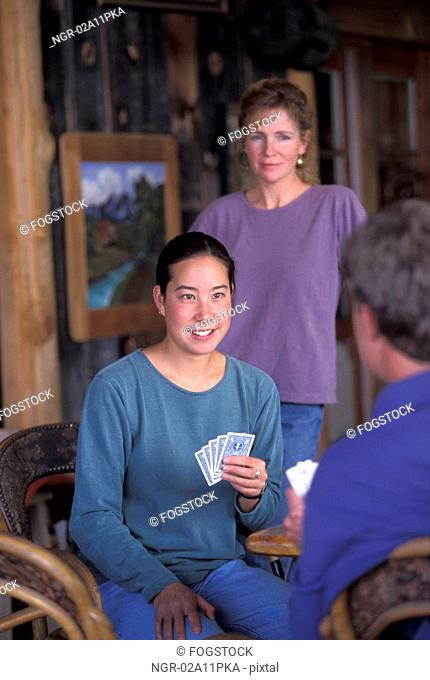 Asian American Woman Sitting In A Cabin And Playing Cards With Friends