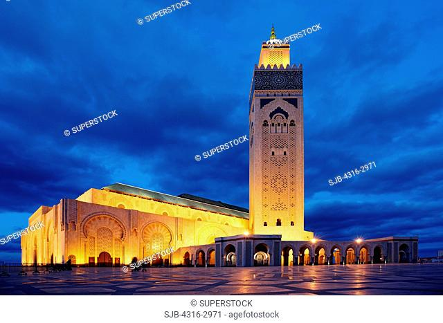 Dusk view of the Hassan II Mosque. The minaret is the tallest in the world at 210 meters high. The laser on the upper minaret emits a green beam which points...