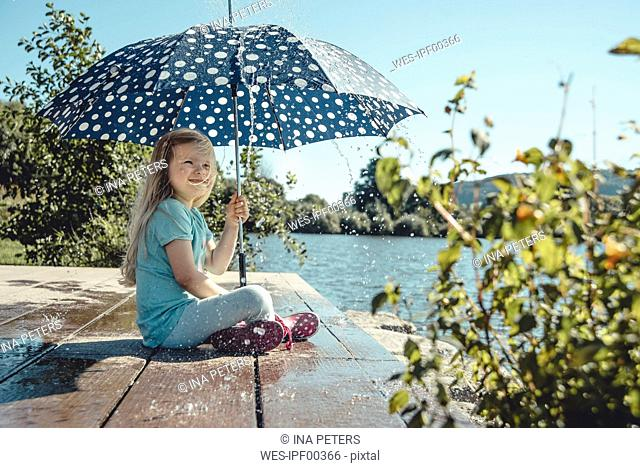 Girl with umbrella sitting on a jetty at lake while waterdrops falling down on her