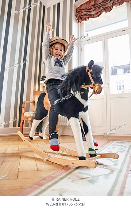 Happy girl posing on rocking horse