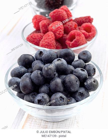 two bowls with blueberries and raspberries on wood
