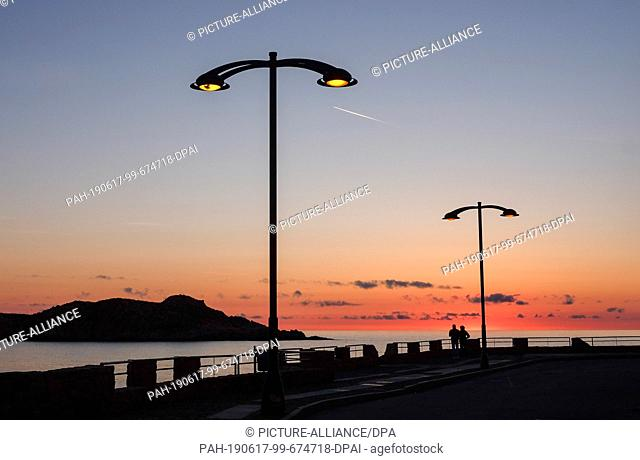 31 May 2019, Italy, Castelsardo: Sunset at the Isola Rossa in the west of the island Sardinia at the beach promenade of the holiday resort Isola Rossa