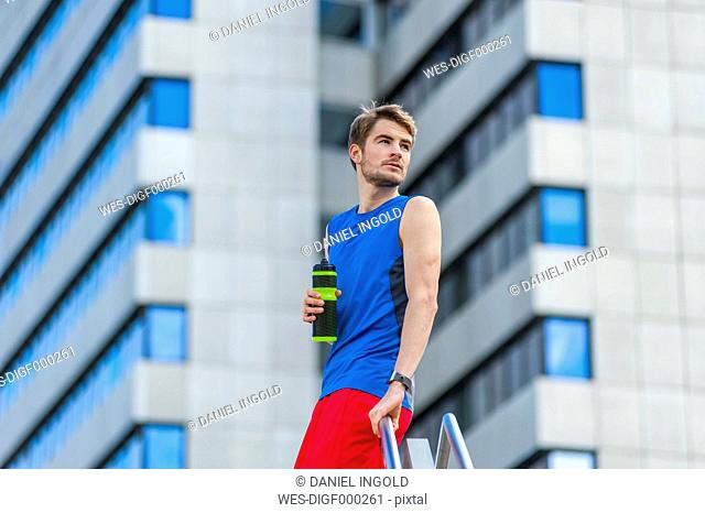 Young sporty man with water bottle and smartwatch
