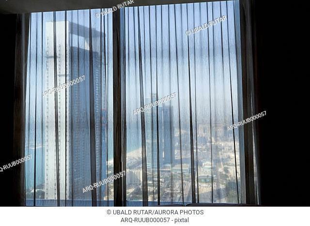 View of skyscrapers of Abu Dhabi through curtain in window, United Arab Emirates