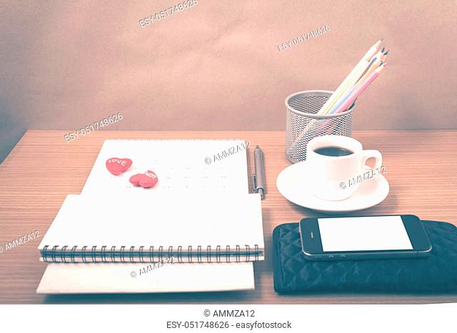 office desk: coffee with phone, wallet, calendar, heart, color pencil box, notepad on wood background vintage style
