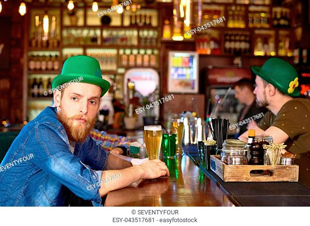 Portrait shot of handsome red-haired man wearing green bowler hat and denim shirt sitting at bar counter and enjoying fresh beer while celebrating St