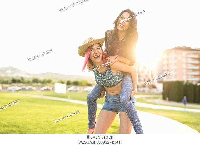 Two girl friends playing piggy back in park