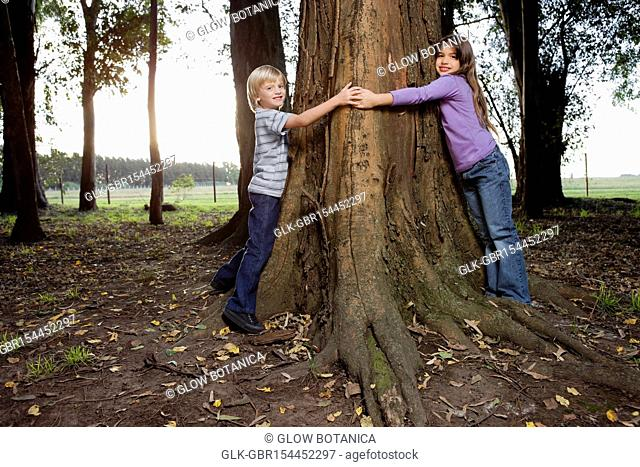 Boy and his sister hugging a tree in a garden