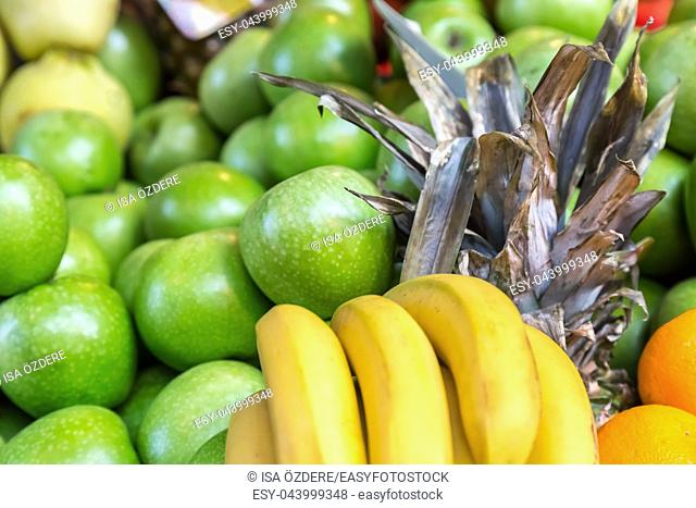 Many fresh bananas,apples and pineapples are sale on a stall at grocery food store