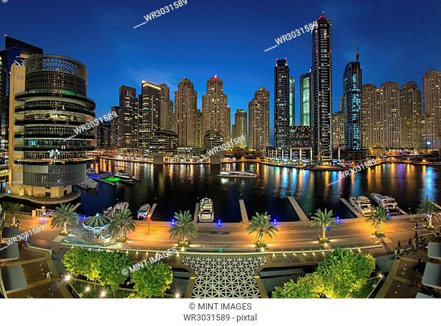 Cityscape of Dubai, United Arab Emirates at dusk, with skyscrapers and the marina in the foreground