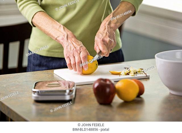 Senior woman cutting fruit