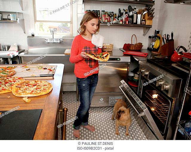 Young girl in kitchen, putting pizza in oven