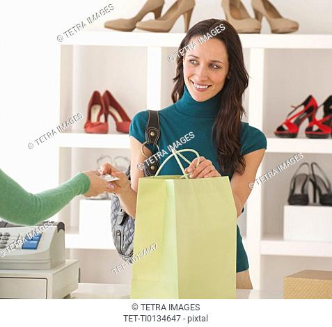 Woman paying for shopping in shoe shop