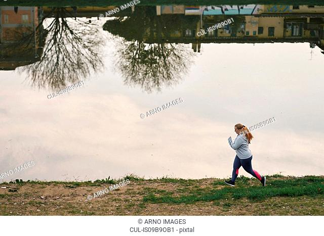 Curvaceous young female runner running on riverside