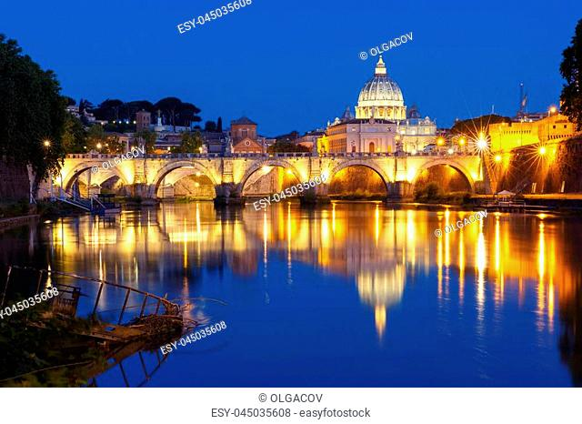 Saint Angel bridge and Saint Peter Cathedral with a mirror reflection in the Tiber River during morning blue hour in Rome, Italy
