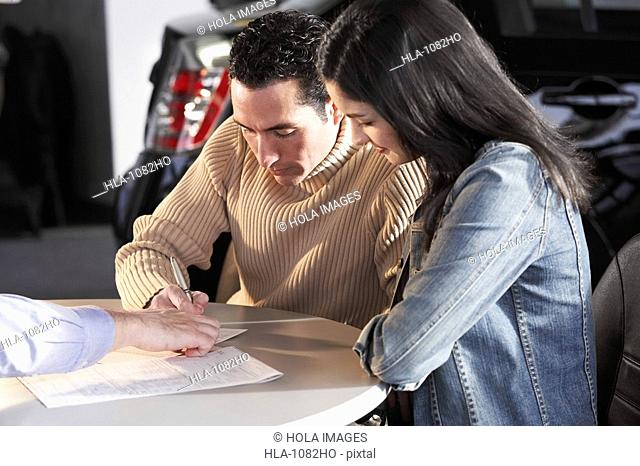 Mid adult man signing a document with a young woman sitting beside him