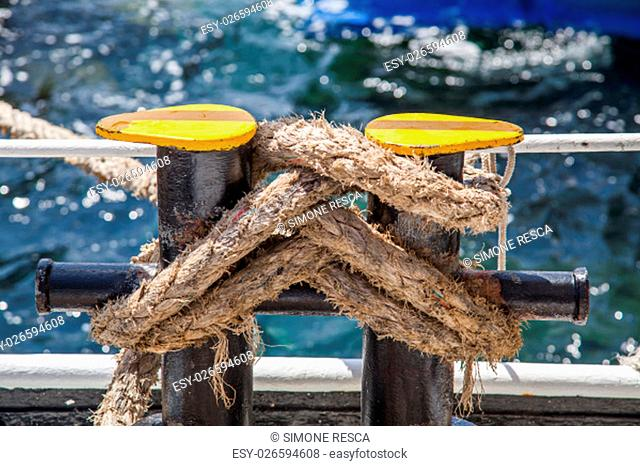 Knotted weathered boat ropes on a blue sea