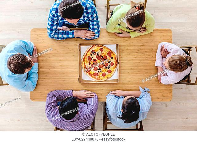 Friends sitting around the table with pizza