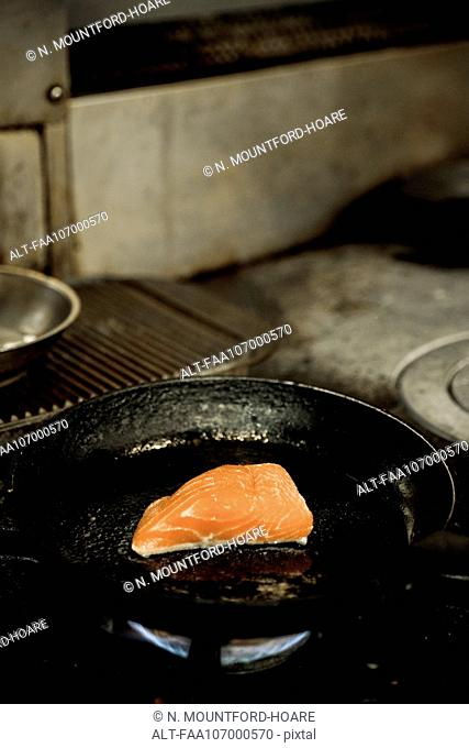Salmon steak frying in pan