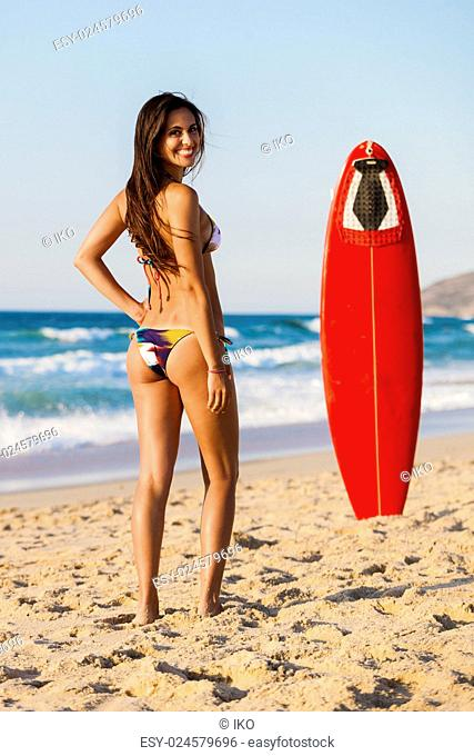 A beautiful girl at the beach posing with her surfboard