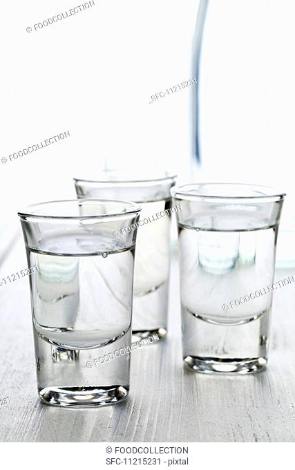 Three glasses of aniseed schnapps (Ouzo) with a carafe of water