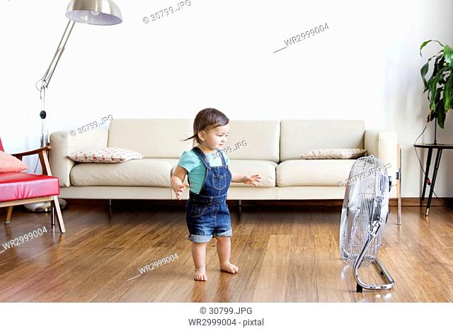 Young boy wearing denim dungarees, standing on hardwood floor in front of electric fan