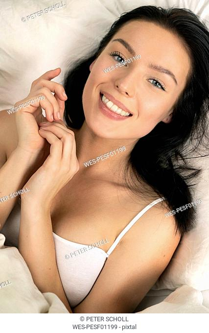 Beautiful woman lying in bed, smiling, portarit
