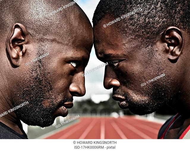 2 male athletes stare, head to head